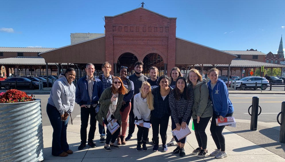 Students from Xavier pose with Detroit Mercy Campus Kitchen student leaders in front of Eastern Market.