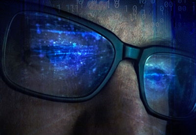 Student looking at Computer code through glasses.