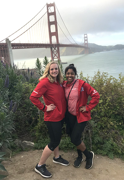 Brynne Gustafson, left, poses with the Golden Gate Bridge in the background during a trip to Stanford University for track and field.