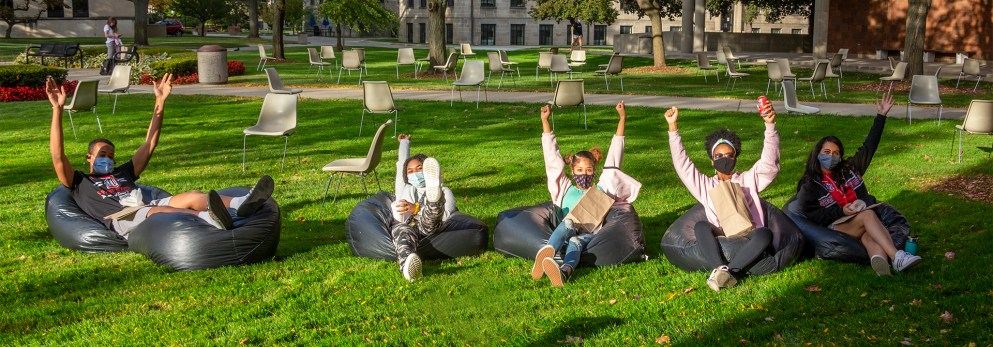 Students socially-distancing and sitting on the McNichols Campus at Fall Festival.
