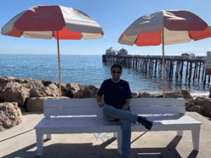 Student AmirReza Radmanesh sitting on a bench at the beach.