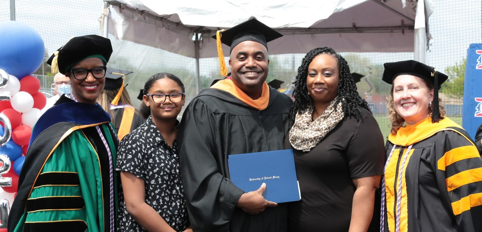 Graduate smiles with his family at on-campus celebration.