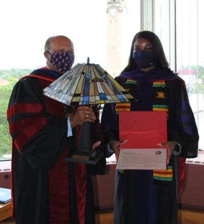 Deja Davis accepts their award from Dr. Garibaldi.