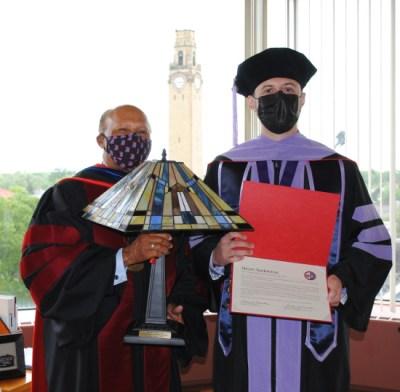 Steven Santarossa accepts their award from Dr. Garibaldi.