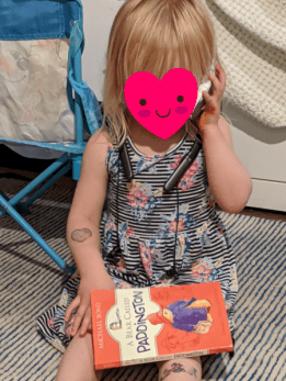 a toddler pretends to be on the phone while reading a book