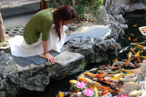 "A woman feeds fish at the Jade Buddha Temple in Shanghai, presenting us with two options: A potentially memorable photo, but also a potentially awkward and uncomfortable conversation. I'm here today to share 10 things you can do to help you approach strangers in foreign countries and go home with the ""people pictures"" you want!"