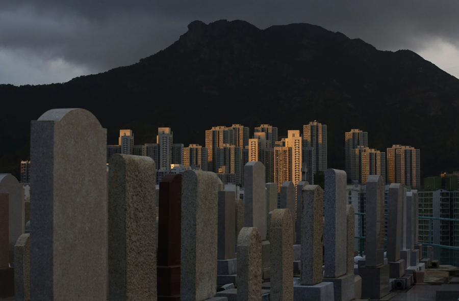 """In this Nov. 19, 2015 photo, graves cover a hillside next to apartment buildings at a cemetery in the Kowloon City district of Hong Kong, where both the living and dead are facing a shortage of space. Limited land to build on and soaring property prices mean Hong Kong is fast running out of space to store the dead. That's a problem for residents who visit grave sites on """"tomb sweeping"""" holidays to burn incense and pay respects to venerated dead ancestors as prescribed by Chinese tradition. (AP Photo/Kin Cheung)"""