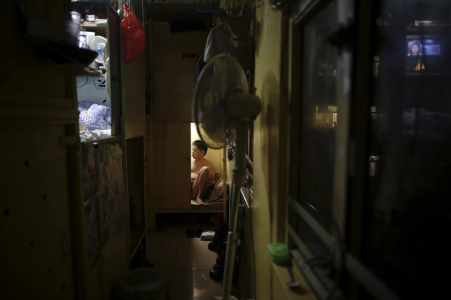 """Akee, 34, who works as a waiter rests in a wooden box that he lives in Hong Kong October 9, 2012. In Hong Kong's middle-class residential area, short distance from its shopping and financial districts, 24 people live in these wooden boxes, or """"coffin homes"""", packed in a single apartment of little over 50 square meters. Its residents pay 1450 Hong Kong dollars ($180) for their living space built of wooden panels of 2 meters by 70 cm. To maximize income from the rent in central Hong Kong landlords build """"coffin homes"""", nicknamed due to their resemblance to real coffins. Space has always been at a premium in Hong Kong where developers plant high-rises on every available inch. REUTERS/Damir Sagolj (CHINA - Tags: SOCIETY REAL ESTATE BUSINESS) - RTR38YAK"""