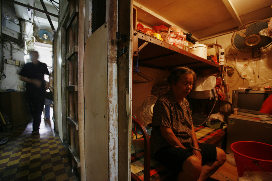 """A woman sits inside her """"cubicle"""" home, one of the 19 24-square feet units inside a 600 square foot residential apartment complex in Hong Kong September 16, 2009. The Hong Kong government estimates that about 100,000 people live in similar """"cubicle"""" units, which cost an average monthly rental rate of $150, in one of the world's largest financial hubs, according to the Society for Community Organization, an NGO which helps those in need. REUTERS/Bobby Yip (CHINA POLITICS BUSINESS SOCIETY) - RTR27WJH"""
