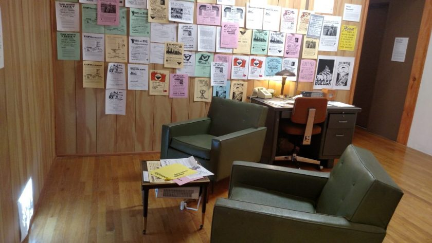 Two green chairs face a wall. Fliers decorate an adjacent wall.