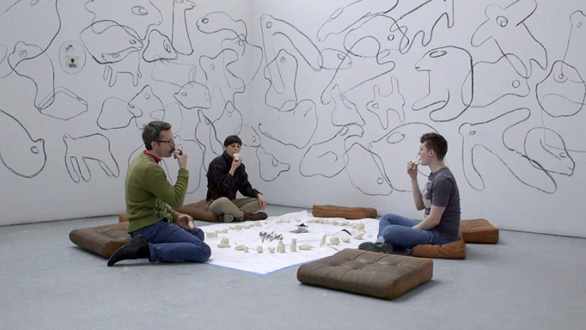 Courtesy of the artist. Three figures sit in the middle of a room in front of several clay whistles. They are each holding one to their mouth.
