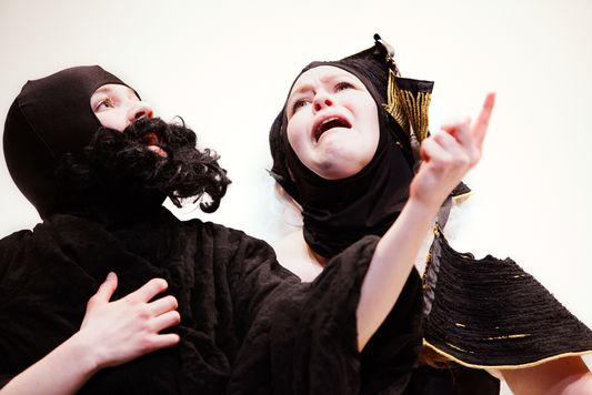 """This is a color photograph still from the performance """"Play."""" Two figures, draped in black clothing are shown. The one on the left is wearing a fake black beard and pointing with their left hand. The one on the right has a black head covering and appears to be wailing in despair."""