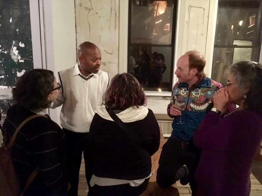 A group of five people talk about the dinner experience. Among them is Elbert Ford. Photo by Tricia Van Eck.