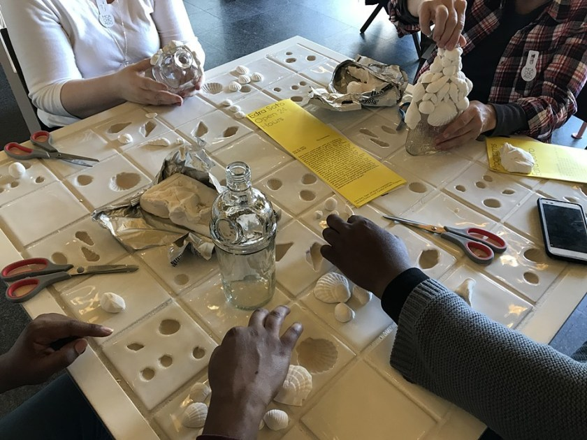 This image shows the hands of four people attaching shells to empty glass liquor bottles. The four people are sitting at a white table that has imprinted moulds in the shape of shells inlaid into its surface. On the table there are shells, empty liquor bottles, scissors, yellow pamphlets, and a cell phone. The activity pictured is part of the workshop series that accompanies Soto's installation at the MCA. Image courtesy of the artist.