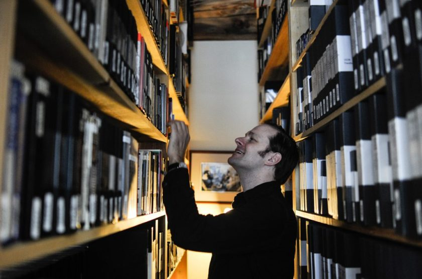 Photo by William Camargo. Dan Erdman at Media Burn is looking at the archival shelfs with one hand on a shelf.