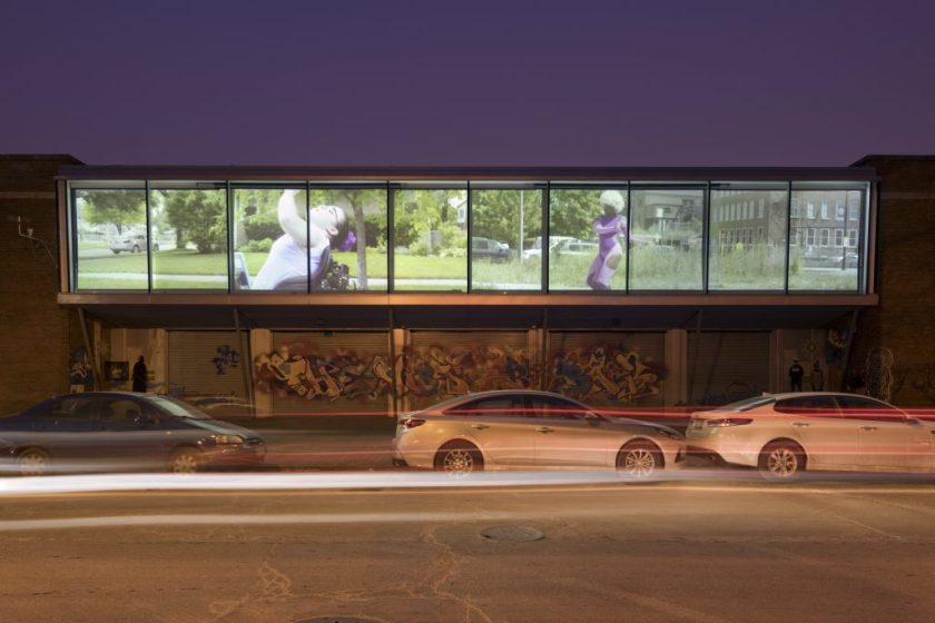 """Justine Pluvinage's """"Amazons"""" as seen from Cornell Ave outside the Hyde Park Art Center. A 10-panel display showing a grassy urban environment and a young woman is projected onto the building's facade. Photographer:"""