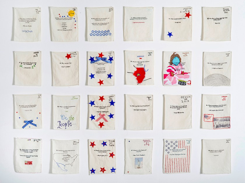 """US Citizenship Test Sampler"" (24 out of 120), 2013–present. Embroidered samplers made by non-citizens who live and work in the U.S. installed in a grid on the wall. Photo by Hyounsang Yoo."