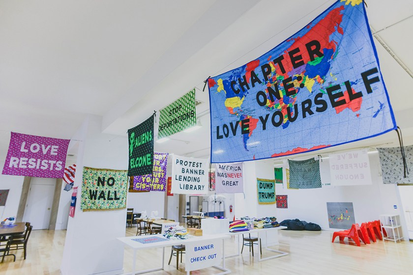 """Protest Banner Lending Library"", 2016–present. Installation of the ""Protest Banner Lending Library"" at the Chicago Cultural Center with protest banners hanging from the ceiling. Some of the most prominent banner read ""CHAPTER ONE: LOVE YOURSELF,"" ""ALIENS WELCOME,"" ""NO WALL,"" and ""LOVE RESISTS."" Photo by eedahahm."