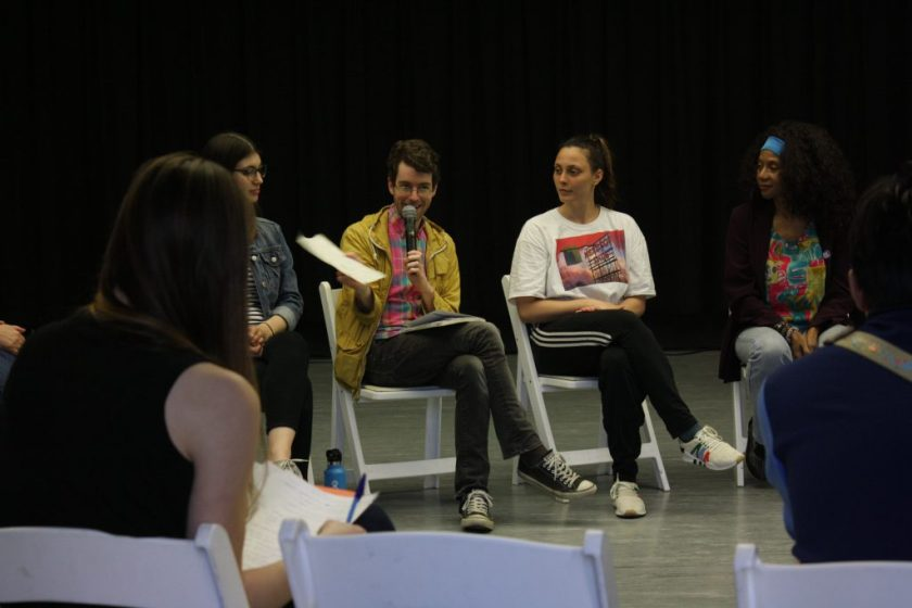 This photo shows some of the discussion's participants. Four of the panelists sit in white chairs in a dance studio, facing the camera, with a black curtain behind them. Two audience members' backs are to the camera. The panelist with the microphone is smiling, holding a piece of white paper in one hand.