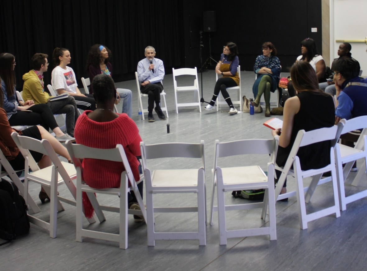 Featured image: This is a photograph of a group of people in a dance studio, sitting in a circle of chairs. Some people have their backs to the camera, and other people are shown straight-on or in profile. The two chairs nearest the camera are unoccupied, creating a window to the speaker, a man holding a microphone. Photograph by Hannah Siegfried.