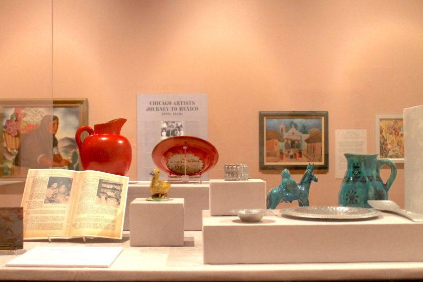 "Detail of a glass case from the exhibition holding silver dishware, ceramic jugs, and ceramic sculptures — one a yellow duck and another a green religious sculpture of Joseph walking behind Mary on a donkey. In the background there is a painting of an indigenous Mexican woman carrying flowers on her back in a basket, four photographs of Mexican artesanos working, and wall text that reads ""Chicago Artists Journey to Mexico."" Image by Jennifer Patiño Cervantes."
