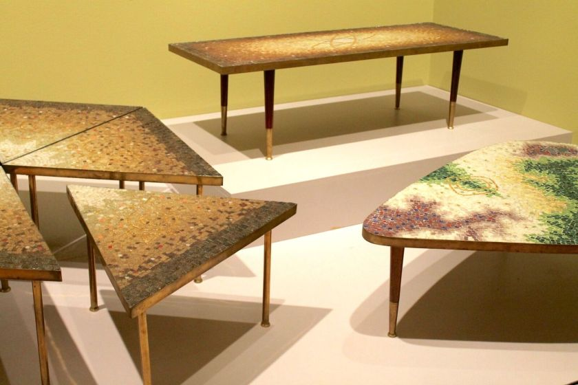 Mosaic tables by Genaro Álvarez . The table furthest back is long and has brown and gold tiles. Another table is a hexagon made up of smaller wedge shaped tables. And the table in the foreground is a triangular shape with rounded corners and red, purple, and green tiles. Image by Melissa Patiño Cervantes.