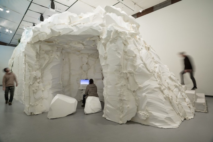 "Installation view of ""who cares for the sky"" at Hyde Park Art Center, 2016. The image shows a large white mountain structure in the middle of a gallery space. Carved into the side is an opening with white rocks where a person is sitting and looking at an image on a screen. Photo courtesy of her website, sabinaott.com."