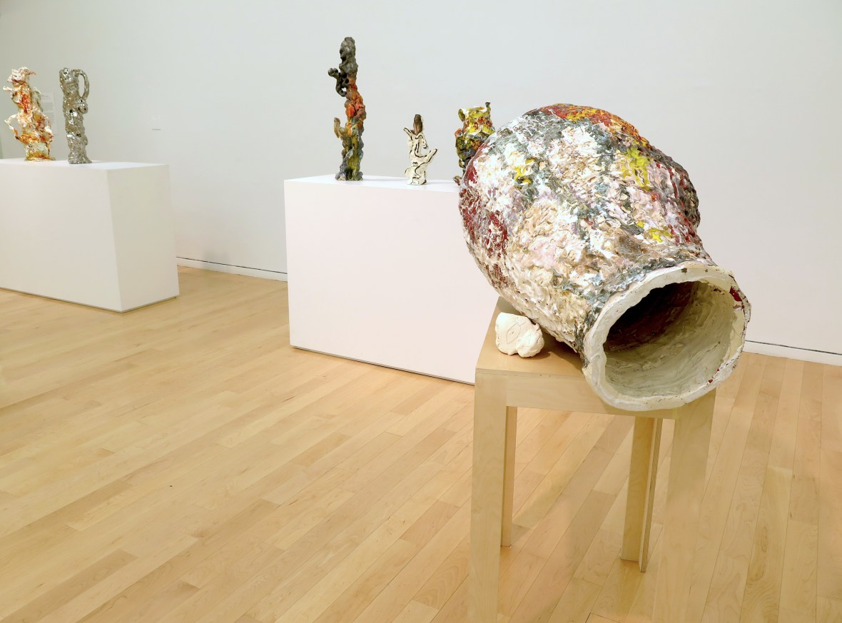 """This photo shows part of the gallery. In the foreground on the right-hand side of the image, """"Goya Dreaming"""" sits on a narrow wood table. The artwork is oblong in shape, with a colorful, textured surface; from this angle, a large opening is visible. In the background are two broad pedestals (partially seen) displaying several sculptural objects."""