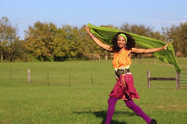 The poet strides across the frame—smiling, brightly-clothed, and with arms spread, a lime-green cloth suspended between her hands and floating behind her. She is outdoors in a grassy field, with a wire and wood fence in the near background and a line of trees farther back. The sky is light blue.