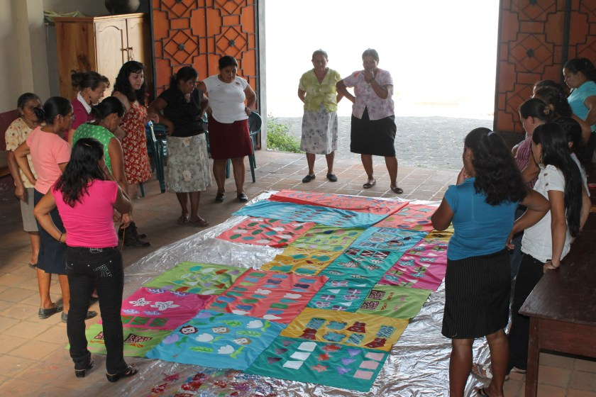 """""""MorazánHilvanando Colores,"""" 2013. Fiber collaboration at Walls of Hope in Perquín, El Salvador. Victoria Martinez is standing with a group of women around a large textile on the floor. The textile is composed of different rectangular fabric pieces of varying vibrant colors that have a range of geometric patterns painted onto them. The piece was collaboratively made by the artists and these women, who have experience with war in El Salvador, from being nurses at war to having relatives to past survivors."""
