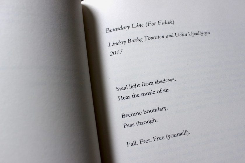 """This image is a close-up photograph of an open book, showing a typed performance score with black text on a white background. In italicized text, it says: """"Boundary Line (For Falak) // Lindsey Barlag Thornton and Udita Upadhyaya / 2017."""" In regular text it says: """"Steal light from shadows. / Hear the music of air. // Become boundary. / Pass through. // Fail. Fret. Free (yourself)."""""""