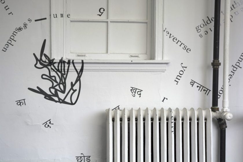 """The photograph shows part of one of the gallery's internal, white walls, including part of a window (with white glass) and radiator, and some piping. Black vinyl letters are installed directly onto these surfaces and the walls, in the form of words and phrases in English and Hindi. Text appears in different sizes and spatial orientations (e.g., right-side up, upside-down, diagonal, vertical, and organic shapes), with some words/phrases expanded in space, condensed, or intersecting with other text. English words/phrases shown in this image include """"5,"""" """"your,"""" and """"sudden."""" A gestural drawing—also made of black vinyl—is shown on the left-hand side of the image."""