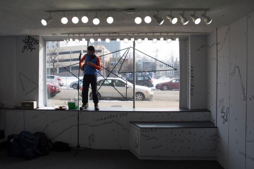 The photograph is a long shot of the inside of the gallery, with the large front window in the background and, beyond that, cars and buildings outside. A performer stands in the windowsill. Around the performer, on the sill or the floor, are a thermos, a microphone on a long stand, and a pile of cloth. Above the performer is a line of track lights that face the camera, in addition to the daylight coming in from outside. Black vinyl letters are installed directly onto the white gallery walls, in the form of words and phrases in English and Hindi. Text appears in different sizes and spatial orientations (e.g., right-side up, upside-down, diagonal, vertical, and organic shapes), with some words/phrases expanded in space, condensed, or intersecting with other text. Gestural drawings—also made of black—are shown on the top left-hand side of the image.