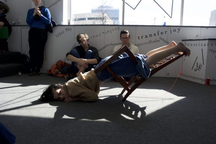 This is a still image of a performance. Tannaz is in the middle of the floor, with hair spread onto and a cheek pressed into the floor. Tannaz faces the camera with eyes closed or cast downward and hands on the floor. Tannaz's body is suspended through the inside of a chairframe—which is suspended at a roughly 45-degree angle—with Tannaz's toes touching the top of the back of the chair. Red thread hangs from parts of the chair and a spool of red thread is in the back by the wall. Audience members sit or stand in the background, leaning against a gallery wall and facing the camera. Words, phrases, and shapes on the gallery wall and front window are visible behind them.