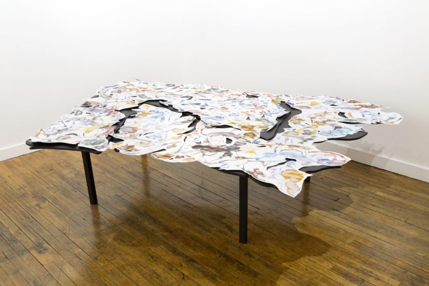 This is a photo of a corner of a gallery space, with a wood floor and with two white walls meeting in the background. In the center is a multi-layered artwork spread across a large black table. The table is asymmetrical, with many curved edges. On the table are several pieces of white paper (also asymmetrical, with many curved edges) covered in gestural drawings of various colors.