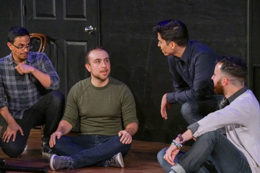 The performers sit or crouch on the stage's wooden floor. Adam, Paul, and Devin look at Alex, whose body is angled toward the camera. Behind the performers is the black wall of the stage, with a part of a black door visible in the frame.
