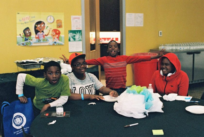 Image: Four children pose for a photo during an arts and crafts activity at BBF Family Services. BBF Family services has been in the same North Lawndale community where the RJCC convenes since 1961, and works to empower children and family in the communities. Photo by Eric K. Roberts.