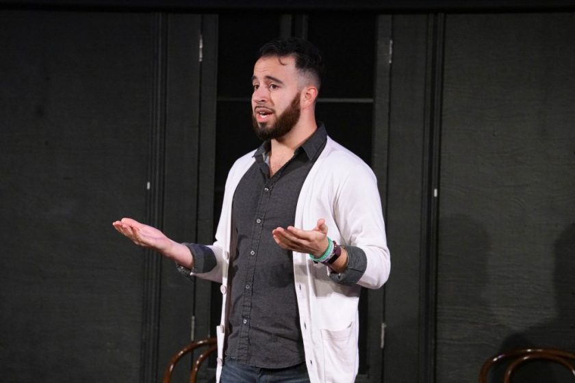 This is a medium-shot of the performer standing onstage. Devin addresses and gestures at the audience. Behind the performer is the black wall of the stage, with part of a black, covered window and two chairs visible in the frame.