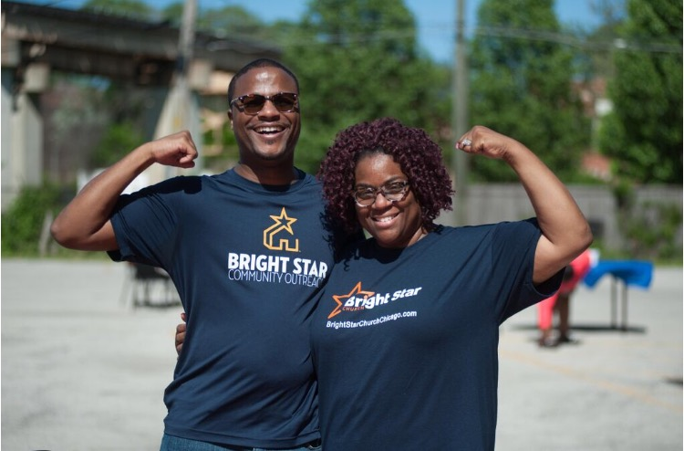 Two members of Bright Star Community Outreach pose with flexed arms