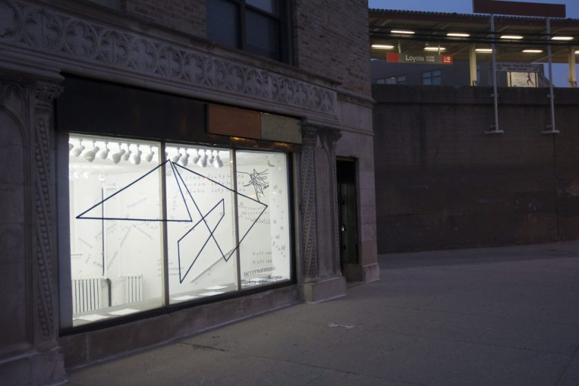 """This is an external shot of the gallery, with the CTA Red Line """"Loyola"""" elevated stop in the background. It is dim outside, and the gallery's lights are on inside. Visible through the gallery's large front window (which is framed by a decorative, stone façade) is the inside of the gallery—bright white walls and fixtures, with black vinyl lettering (English and Hindi) and shapes (triangular and gestural)."""