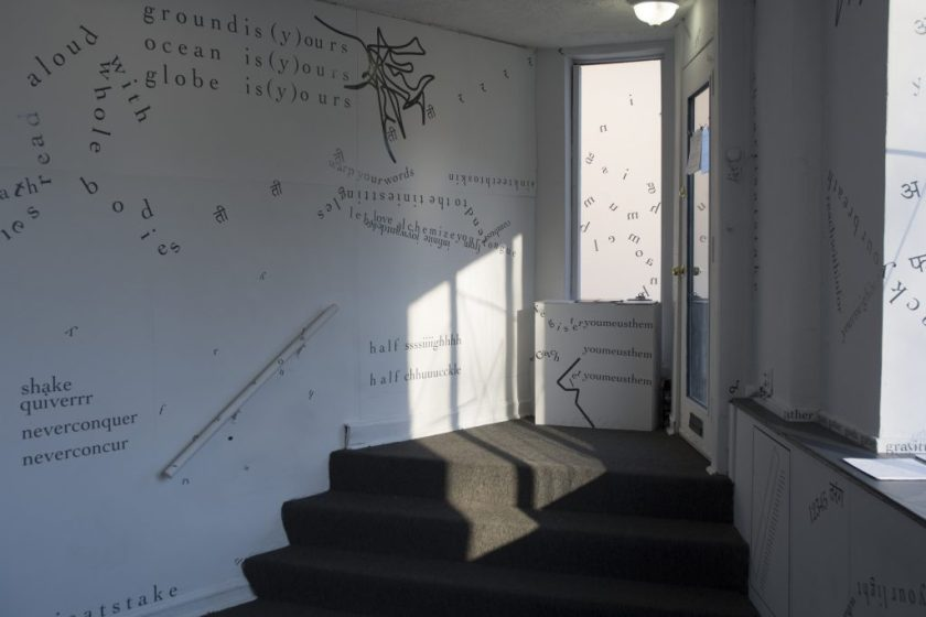 The photograph shows parts of gallery walls as well as the triangular entry-way, with no people present. In the center of the image, there are three grey, carpeted stairs descending from the entry-way into the gallery space. Light from the door's window casts sharp shadows onto a wall, the floor, and the stairs. Black vinyl letters are installed directly onto the white gallery walls, in the form of words and phrases in English and Hindi. Text appears in different sizes and spatial orientations (e.g., right-side up, upside-down, diagonal, vertical, and organic shapes), with some words/phrases expanded in space, condensed, or intersecting with other text. Gestural drawings — also made of black vinyl — are shown near the center of the image.