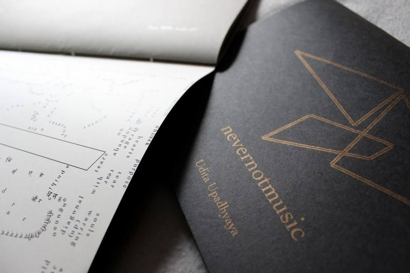 """This image depicts part of a performance score (bound into a thin book) and most of a cover (""""nevernotmusic"""" and """"Udita Upadhyaya"""" in gold text, with thin parallel gold lines forming two triangles and a rhombus, on black paper). On the bottom page are text in English and Hindi and a hollow shape (partially visible; possibly a rhombus), both in black ink against a whitish vellum background. Text appears in different sizes and spatial orientations (e.g., right-side up, upside-down, diagonal, vertical, and organic shapes), with some words/phrases expanded in space, condensed, or intersecting with other text. Along one side of the vellum page, text is flush with the edge; along the binding side, there is a white margin between the line of text and the binding. The top page is grey with a short line of black text (not readable in this image) that reflects the light."""