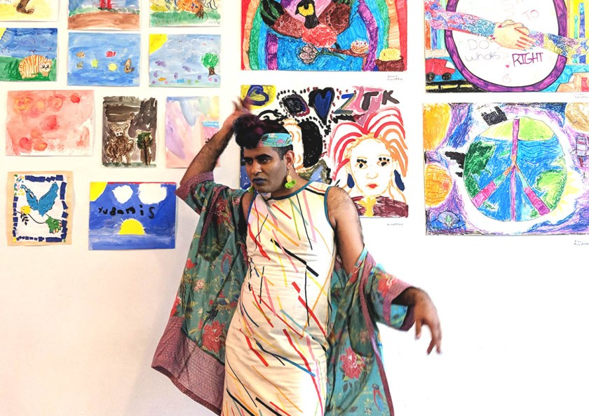 Image: Alok Vaid-Menon poses in front of a wall of colorful artwork at AMFM gallery in Pilsen before their show. They are looking away from the camera, standing statuesque with one arm lightly rested on their front top bun, hand facing up, and their other arm casually extended, in soft motion, like a queen expressing a need. Photo by Chelsea Ross.