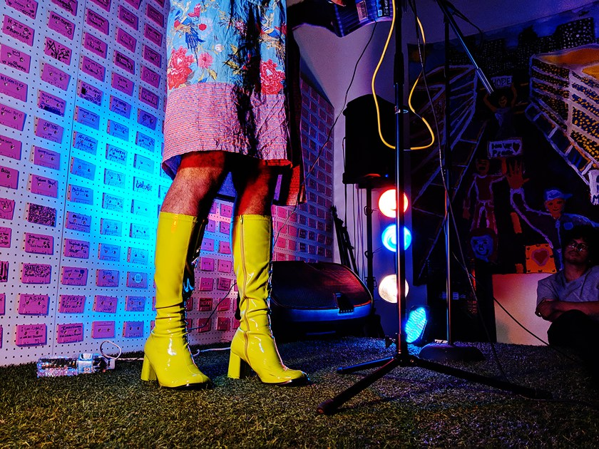 Image: Alok's lime green, patent leather gogo boots stand out on astroturf covered stage. Photo by Chelsea Ross.