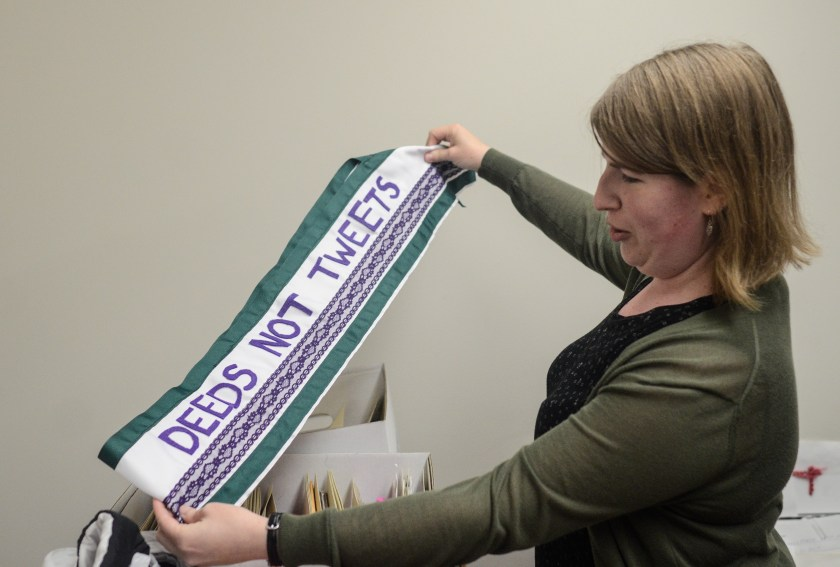 "Image: Catherine Grandgeorge holds up a green, white, and purple sash that says ""Deeds Not Tweets"" with both arms. Image by William Camargo."