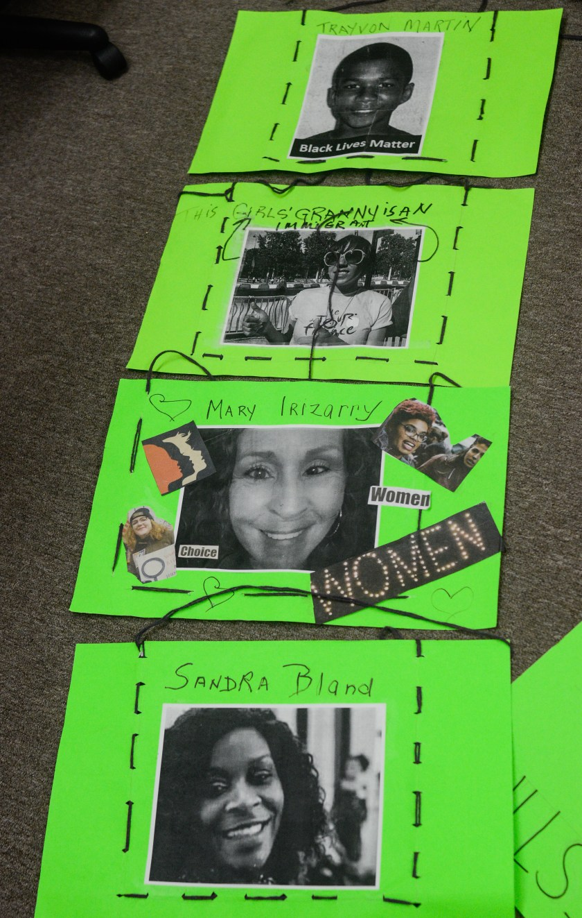 "Image: Four green poster boards are stitched together with black thread. It appears designed to be draped across the front and back of the body. Photos are accompanied with text on each sign. From top to bottom, the text reads ""Trayvon Martin,"" ""This Girls' Granny is an Immigrant,"" ""Mary Irizarry,"" along with ""Women"" and ""Choice,"" and lastly ""Sandra Bland."" Image by William Camargo."