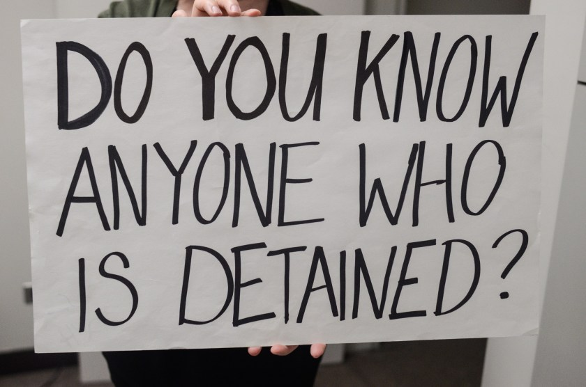 "Image: Catherine Grandgeorge holds up a white sign with black lettering that reads ""Do You Know Anyone Who Is Detained?"" that was used at airports by lawyers responding to the travel ban. Image by William Camargo."