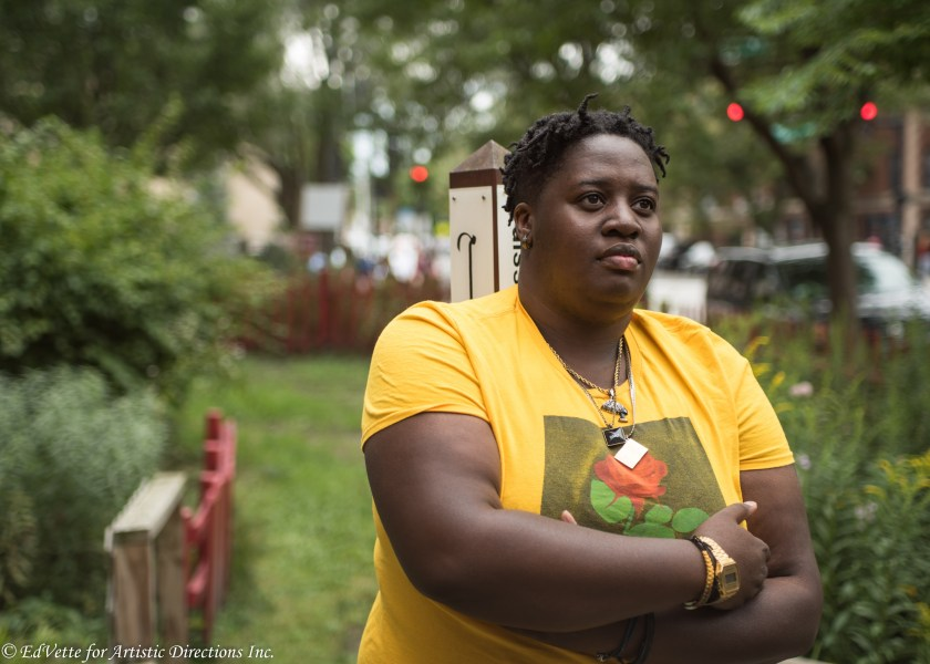 IMAGE: AnnMarie Brown stands in front of a garden area near the entrance of United Church of Rogers Park. She is staring away from the camera with arms slightly folded wearing a yellow shirt with a red rose imprint on the front.
