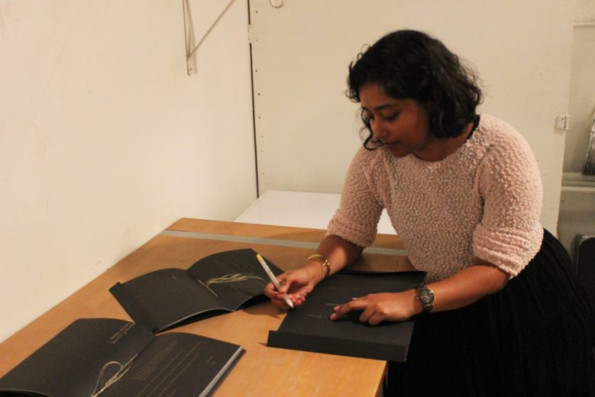 """Image: Udita Upadhyaya at the book release for """"nevernotmusic."""" The artist leans over a table, looking down as she writes in gold pen inside a copy of her book. Next to Udita are two other copies, open to their centerfolds, where gold thread is visible. The artist wears a light-colored, textured sweater and black skirt. Photo by Caleb Neubauer."""