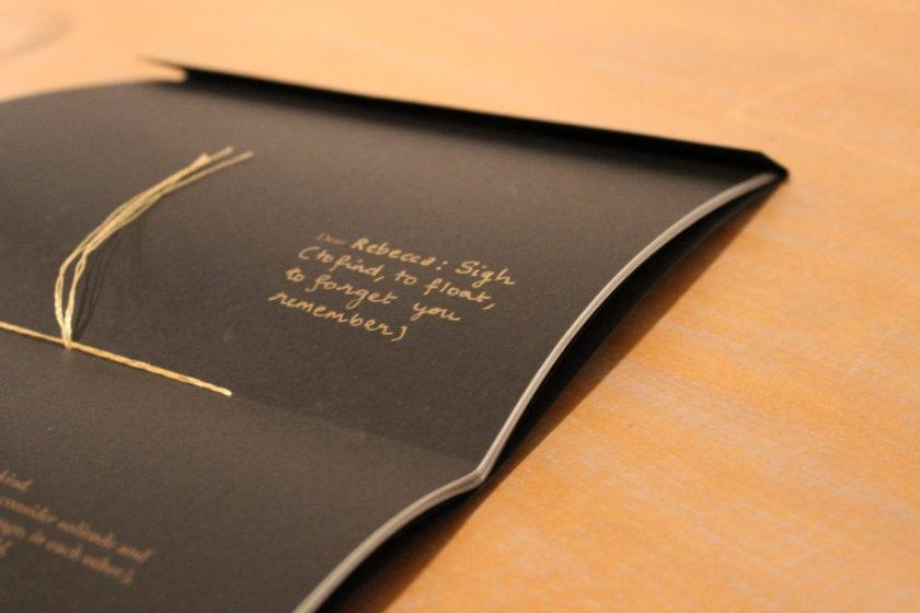 """Image: Udita Upadhyaya's book """"nevernotmusic"""" (detail). On a wooden tabletop, the book lies open to the centerfold, showing black paper, gold thread, and gold writing. The word """"Dear"""" is legible in gold type, followed by gold handwriting: """"Rebecca: Sign (to find, to float, to forget you remember)."""" Photo by Caleb Neubauer."""